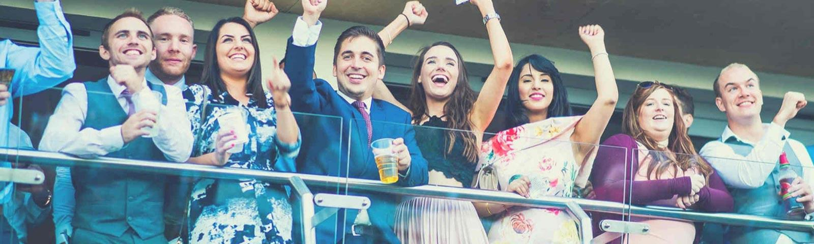 Friends cheering as they enjoy quality racing at Bath Racecourse.