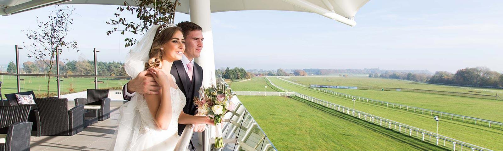 A couple of newlyweds standing on the Roof Garden terrace looking at the Bath Racecourse track.