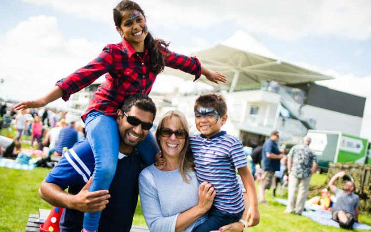 Family posing for a photo during a family fun day at Bath Racecourse.