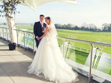 Newlywed couple standing on a balcony at Bath Racecourse.