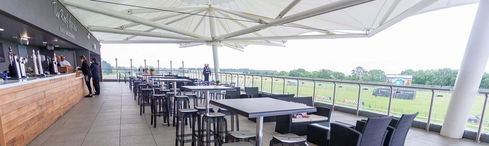 View of the Roof Garden bar at Bath Racecourse, with rows of tables set up alongside the bar.