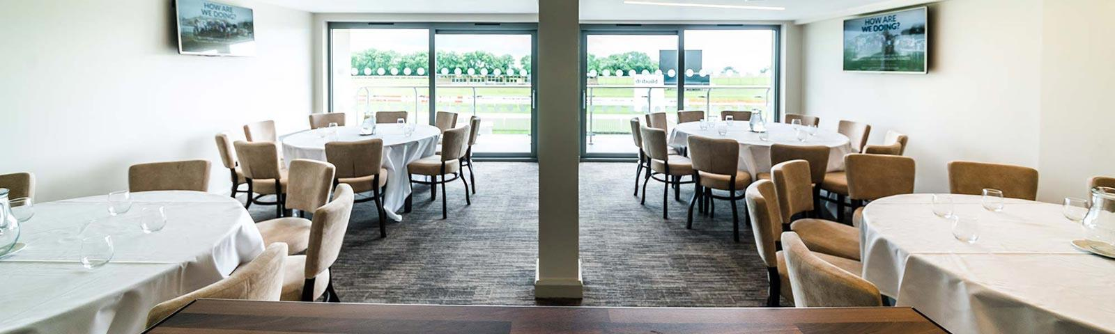 Private room at Bath Racecourse set up with tables and chairs.
