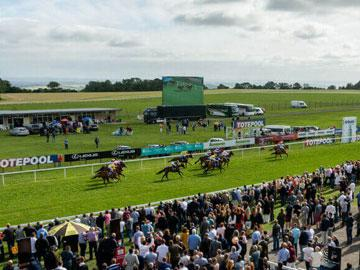 Jockeys racing past the crowds at Bath Racecourse.
