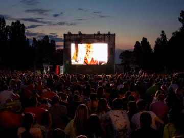 A crowd of people enjoying a movie at an outdoor cinema.