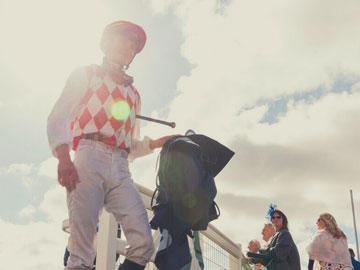 Jockey walking through parade ring at Bath Racecourse.
