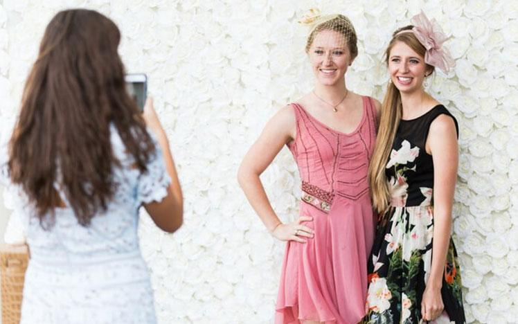 Two ladies posing for a photo during a raceday at Bath Racecourse.