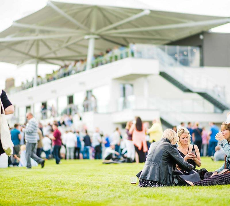 Crowds sitting on the grass outside of the main grandstand at Bath Racecourse.