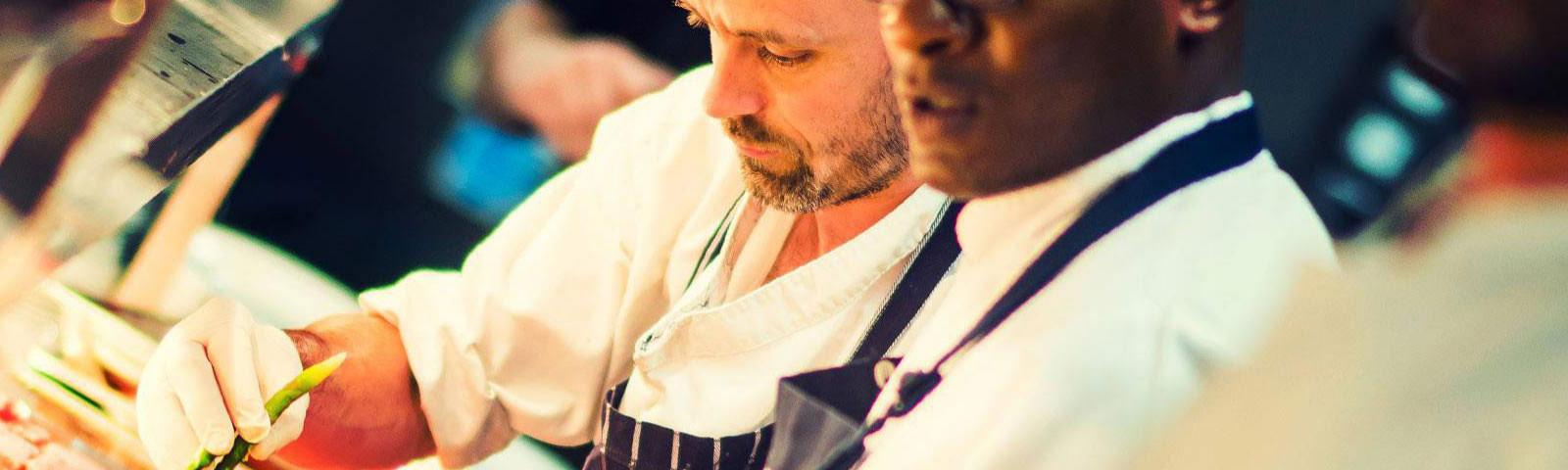 Two chefs preparing food.