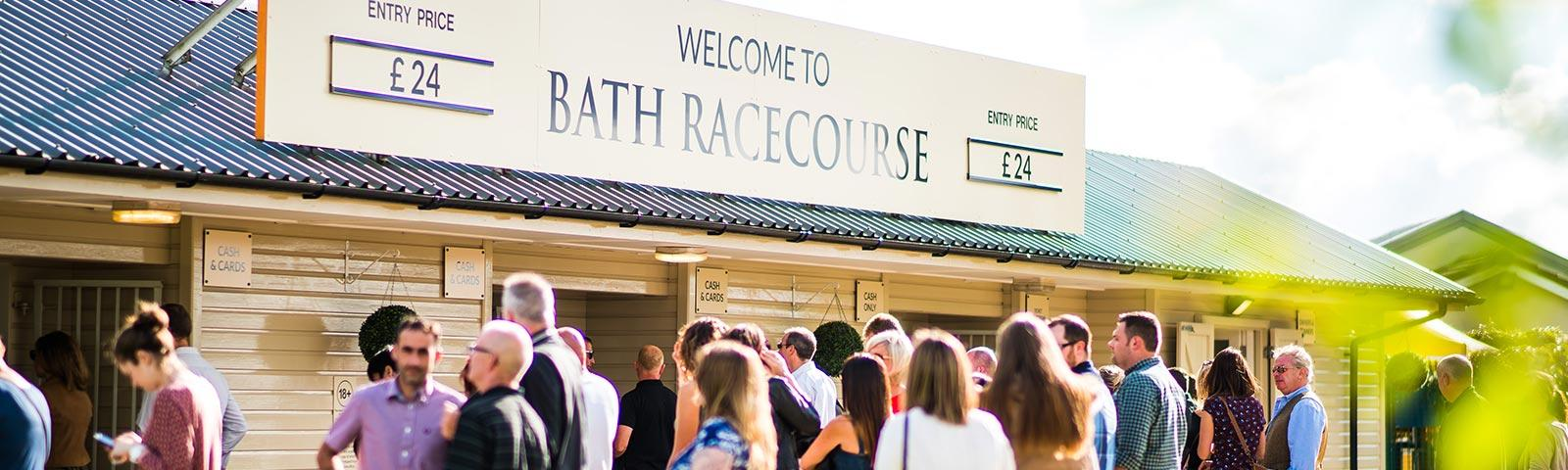 Main entrance to Bath Racecourse, with visitors lining up to get inside.